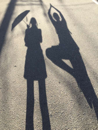 Shadow of a women holding an umbrella while a man is making the yoga tree pose beside her