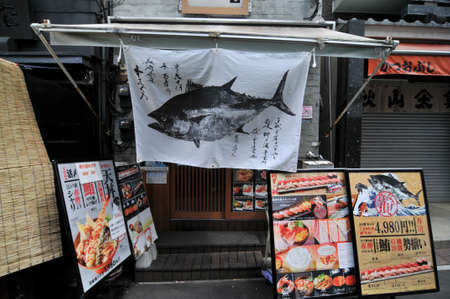 TOKYO, JAPAN - 11th JULY 2018 : A typical japanese drape, with a tuna logo, hanging at the entrance porch of a restaurant in the famous Tsukiji Fish Market area in Tokyo, Japan