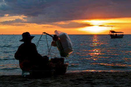 Silhouette of a traditional female shrimp / crayfish vendor at Otres Beach (Sihanoukville) in Cambodia at sunset Stock Photo