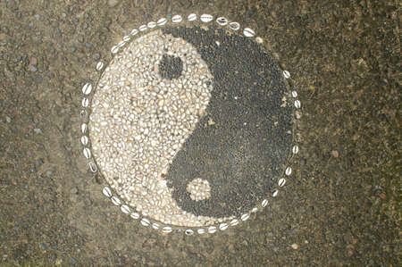 Picture of Yin-yang symbol made of little stone pebbles located outside a restaurant in Ubud, Bali Stock Photo