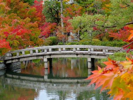 Hermosos colores otoñales en el templo Eikando de Kioto con un puente de piedra en el fondo