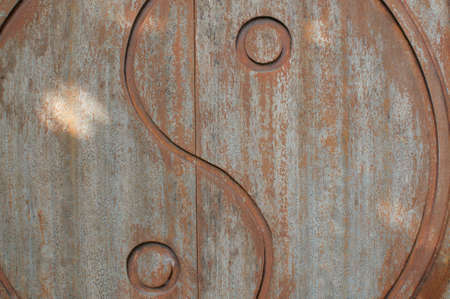Close up of a Yin-yang symbol beautifully carved on a wooden weathered door