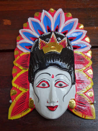 A typical colorful Balinese carved wooden mask used to mark the female restroom
