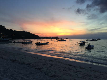 Beautiful sunset at the Beach of Jungtu Batu Bay with many boats anchored in the water on Nusa Lembongan in Bali, Indonesia