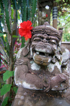 Typical Balinese Dvarapala stone statue with a red hibiscus flower, captured in a park in Ubud on Bali, Indonesia
