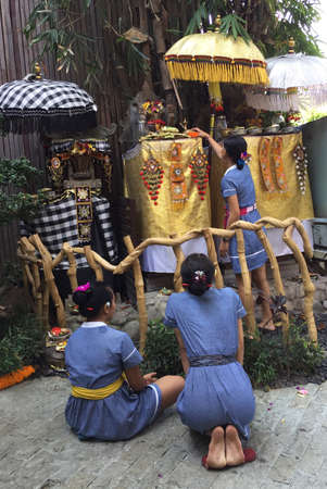 Picture of three women in front of a traditional small shrine before a prayer. Captured in Ubud, Bali, Indonesia
