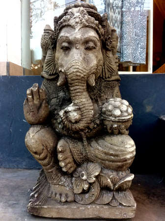 Beautiful Ganesha stone statue in front of a house in Ubud village in Bali, Indonesia