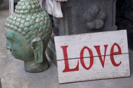 Side view of a beautiful stone Buddha head and a wooden Love sign place in front of a shop in Ubud, Bali - Indonesia