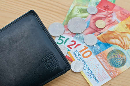 Top view of a black wallet and Swiss currency on a wooden table Reklamní fotografie