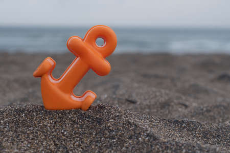 Close up picture of a small orange anchor beach toy placed on the black sand at the Batu Bolong beach in Canggu, Bali during a cloudy day