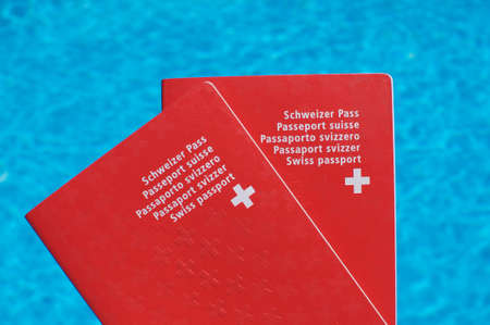 Two Swiss passport held in front of blue pool water background 免版税图像