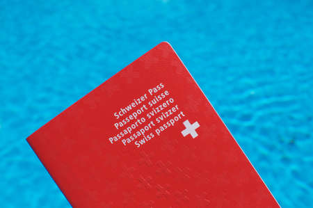 One Swiss passport held in front of blue pool water background