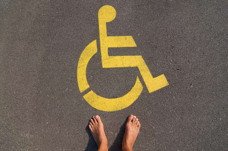 Picture of man standing in front of a yellow disable handicap parking sign drawn on the asphalt of a street in Caslano, Ticino - Switzerland
