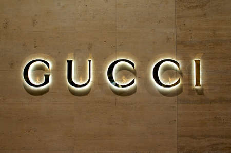 Lugano, Ticino, Switzerland - 12th July 2019 : View of the Illuminated Gucci sign in the City of Lugano, Switzerland. Gucci is know for his luxury leather and fashion goods.