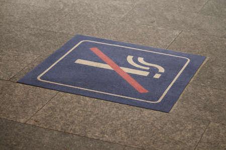 No smoking symbol drawn on the stone ground of the SBBCFFFFS train station of Lugano, Switzerland Stock fotó