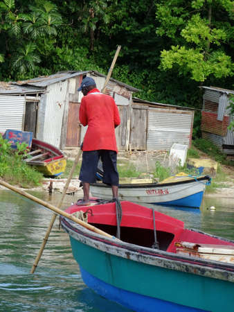Boston Bay, Portland, Jamaica - 12th June 2017 : View of a Jamaican Fisherman paddling on his boat on the Boston Bay river in Portland area with some hovels in the background