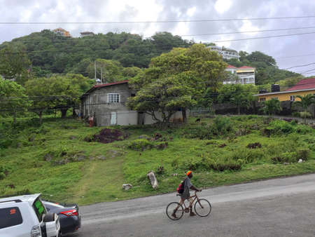 Fairy Hill, Portland, Jamaica - 15th June 2017 : View of a typical house surrounded by the green nature and a Jamaican men pulling his bike uphill on a road in the village of Fairy Hill in Jamaica Stock Photo