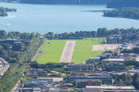 Areal view of the Lugano-Agno Airport runway on a sunny day with the lake Lugano in the background