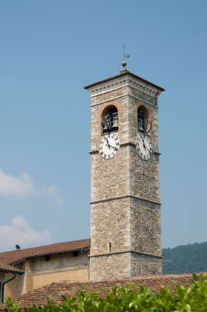 Picture of the Bell Tower of the church San Cristoforo (Saint Christopher) in the village of Caslano against the blue sky, located in the touristic canton Ticino in Switzerland