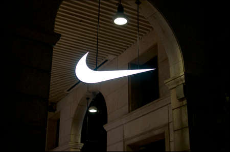 Milan, Lombardy, Italy - 11th September 2019 : Illuminated Nike logo sign hanging from a ceiling in the city of Milan, Italy Editorial