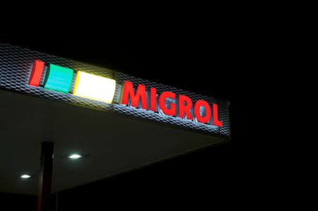 Agno, Ticino, Switzerland - 2nd October 2019 : View of the luminous Migrol gas station in Agno, Switzerland. Migrol is a company owned by Migros, the leading supermarket chain of Switzerland