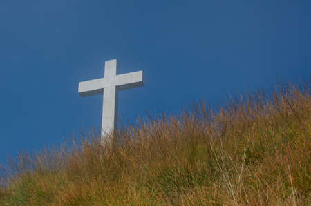 White religious cross against the blue sky and located on the peak of Mount Lema in Switzerland. This is a symbol of hope and salvation