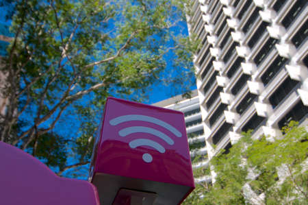 Brisbane, Queensland, Australia - 7th November 2019 : Purple colored WiFi sign of the Telstra company installed on the top of a phone booth in the city of Brisbane, Australia