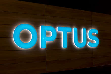 Brisbane, Queensland, Australia - 20th December 2019 : Illuminated Optus sign hanging in front of a store in Brisbane. Optus is the second largest telecommunications company in Australia