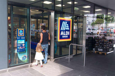 Lugano, Ticino, Switzerland - 19th August 2019 : People entering a Aldi supermarket shop in Switzerland. ALDI is a german company and one of the biggest discount supermarket chains in the world Editorial