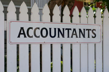 View of an Accountants sign hanging in front of a white wooden fence in Bangalow, Australia