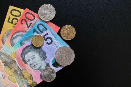 Close up picture of Australian banknotes and coins on a black background. Currency and money from Australia