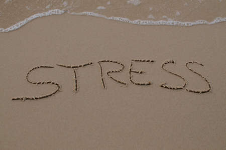 Stress text inscription drawn in the sand with coming water