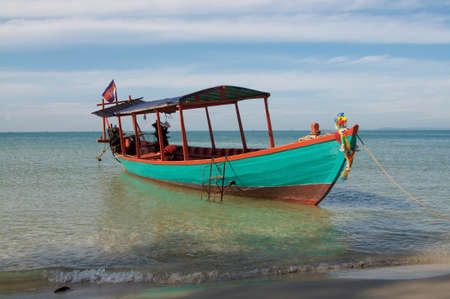 View of a typical cambodian long-tale boat anchored on the beach of Otres near Sihanoukville. This boat is used for the touristic transfer from the mainland to the touristic island of Koh Rong Stock Photo