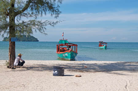 Otres Beach, Sihanoukville, Cambodia - 30th December 2018 : Beautiful seashore of Otres beach with a boatman sitting on the white sand and two typical long-tale boats in the background 報道画像