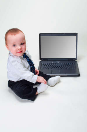 Cute baby businessman working on his laptop with a blank screen Stock Photo