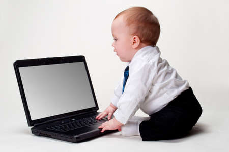 Cute baby businessman next to his open laptop with blank screen ready for your text or artwork.
