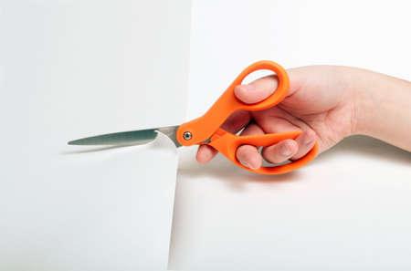 Orange handled scissors cutting through white paper Stock Photo