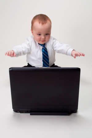 cute baby businessman excited about what he sees on his laptop Stock Photo