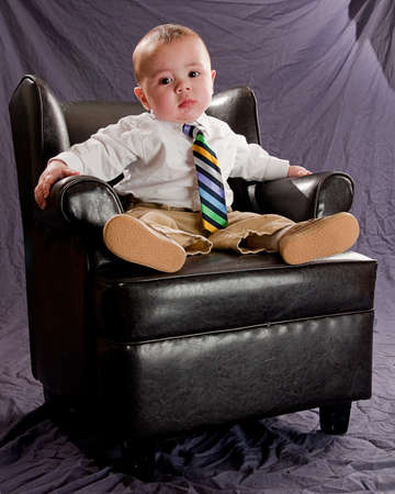 Baby wearing a colorful neck tie, bored expression sitting in a leather chair
