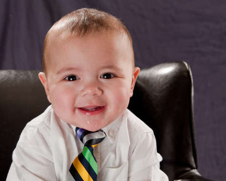 Baby wearing a colorful neck tie smiling  and laughing sitting in a leather chair Stock Photo - 7479497