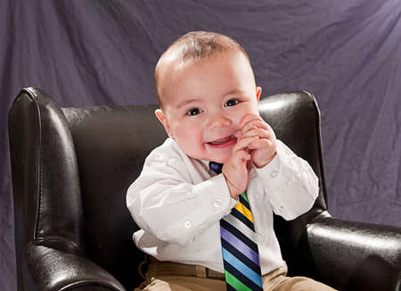 Baby wearing a colorful neck tie smiling and laughing sitting in a leather chair