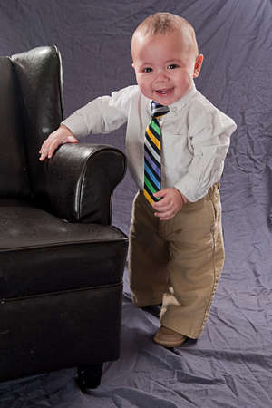 Baby wearing a colorful neck tie smiling and laughing standing next to a leather chair Stock Photo