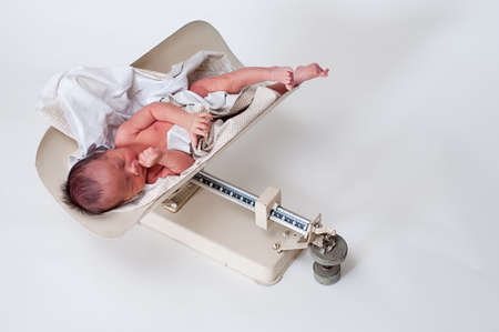 Neborn baby in a vintage scale being weighed Stock Photo