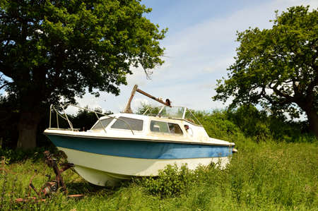 Close up of an abandoned cabin cruiser boat in a field.