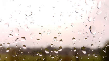 Close up shot of rain on a window with light cloudy sky.