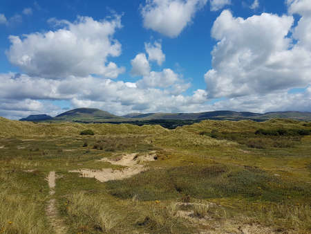 Landscape scene across the sand dunes of Talybont beach in North Wales on a summer day. Imagens