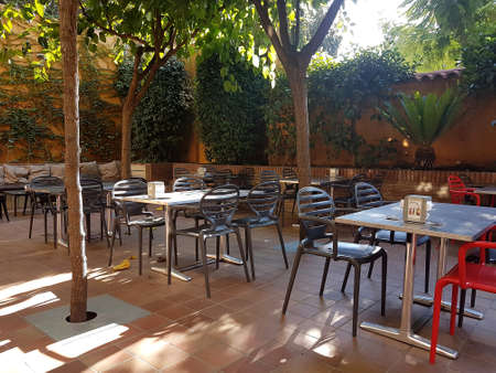 Sitges, Spain - September 20, 2018: Empty table and chairs in an outside restaurant courtyard.
