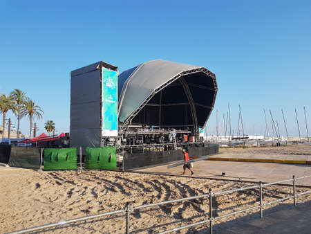 Sitges, Spain - September 20, 2018: Beach scene on a sunny day in Sitges, Spain. A stage is set-up for a concert on the beach.