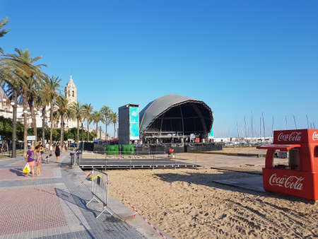 Sitges, Spain - September 20, 2018: Sitges beach scene with a stage set-up on the beach and church in background.