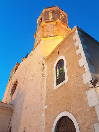 Sitges, Spain - September 20, 2018: Close shot looking up at the church of Sant Bartomeu and Santa Tecla in Sitges, Spain with bright blue sky background.